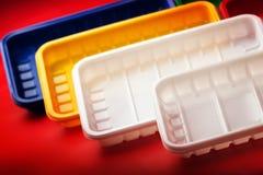 Kulöra plast-plattor på röd bakgrund Fotografering för Bildbyråer