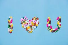 Kulöra preventivpillerar i form ÄLSKAR JAG DIG på blå bakgrund Fotografering för Bildbyråer
