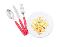 Kulöra preventivpillerar på en vit platta Fotografering för Bildbyråer