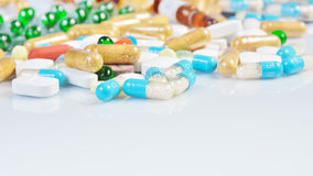 Kulöra preventivpillerar som isoleras på vit bakgrund Arkivbild