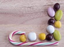 Kulöra sötsaker som fodras på en trätabell Royaltyfri Foto