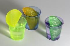 Kulöra skottdrinkar med återvinningsbara iskuber som isoleras Royaltyfri Foto