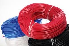 Kulöra spolar av kabel på en vit bakgrund Arkivfoto