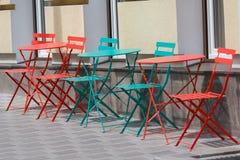 Kulöra tabeller och stolar av ett gatakafé Royaltyfria Foton