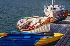 Kulöra trämålade fartyg och en yacht i vattnet av Blacket Sea nära däcket svänger på vågorna Arkivbilder