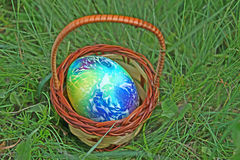 Kulört easter ägg i korg Arkivbild