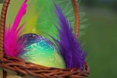 Kulört easter ägg i korg Arkivfoto