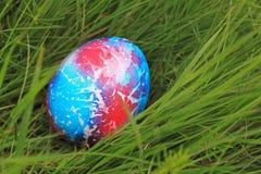 Kulört easter ägg på grönt gräs Arkivfoton
