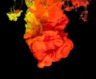 Kulört färgpulver i vatten som skapar abstrakt form Arkivbilder