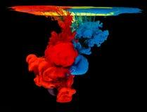 Kulört färgpulver i vatten som skapar abstrakt form Arkivfoton