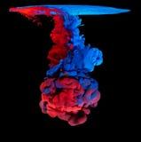 Kulört färgpulver i vatten som skapar abstrakt form Arkivbild