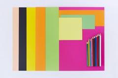 Kulört papper och färgade blyertspennor på vit bakgrund Fotografering för Bildbyråer