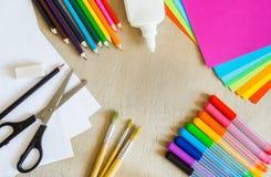 Kulört papper, tuschpennor, blyertspennor, borstar på träbakgrund Arkivbild