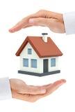 Kulört privat hus mellan två (isolerade) affärsmanhänder, Arkivbilder