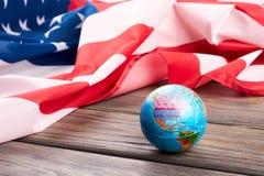 Kula ziemska i flaga amerykańska na drewnianym tle Obraz Royalty Free