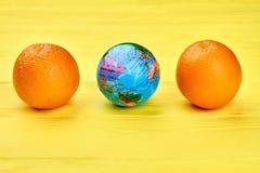 Kula ziemska i pomarańcze na kolorowym tle Zdjęcia Stock