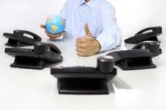 Kula ziemska jak ręka z biurowymi telefonami na biurku i, globalny internati Fotografia Royalty Free