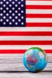 Kula ziemska na stole z usa flaga w tle Fotografia Stock