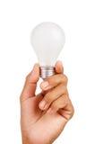 kulahand som rymmer glödande lampa Arkivbild