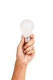 kulahand som rymmer glödande lampa Arkivfoton