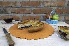Kulebiak, kawałek jabłczany kulebiak z, filiżanka herbata, nóż i jabłka w koszu na stole, wiśnią i orzechami włoskimi, fotografia stock