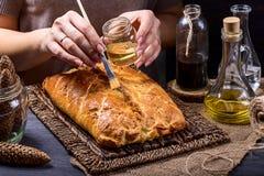 Kulebiak smarujący z oliwa z oliwek na brown tle zdjęcia royalty free