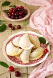 Kulebiaki z wiśniami, kropić z sproszkowanym cukierem i jagodami świeże wiśnie na drewnianej powierzchni zdjęcia stock