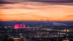 Kuli ziemskiej areny budynek iluminujący w menchiach przeciw zmierzchu niebu podczas Bożenarodzeniowego sezonu wakacyjnego Fotografia Stock