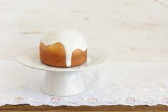 Kulich, traditional Russian easter cake with royal icing on whit. E pedestal and white cloth with space Royalty Free Stock Image
