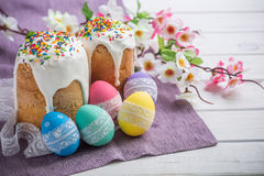 Kulich, traditional Russian Ukrainian Easter cake with icing and colored eggs with lace ribbon on white wooden background royalty free stock photos