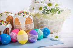 Kulich, traditional Russian Ukrainian Easter cake with icing and colored eggs with lace ribbon on white wooden background. Kulich, traditional Russian Ukrainian Stock Photo