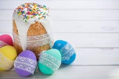 Kulich, traditionele Russische Oekraïense Pasen-cake met suikerglazuur en gekleurde eieren met kantlint op witte houten achtergro Stock Foto's