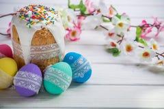 Kulich, traditioneller russischer Ukrainer-Ostern-Kuchen mit Zuckerglasur und farbigen Eiern mit Spitzeband auf weißem hölzernem  Stockfoto