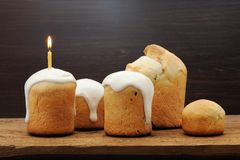 Kulichi, traditional Russian Easter cake with icing and candle  Royalty Free Stock Photos