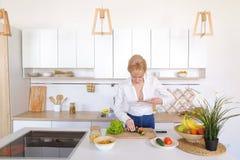 Kulinarisches Mädchen hält Smartphone in den Händen und macht Foto von veget Lizenzfreie Stockfotos