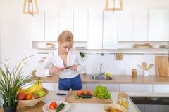 Kulinarisches Mädchen hält Smartphone in den Händen und macht Foto von veget Stockbilder