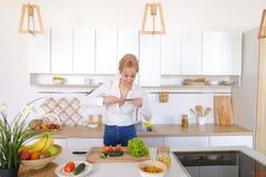 Kulinarisches Mädchen hält Smartphone in den Händen und macht Foto von veget Stockfoto