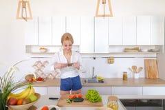 Kulinarisches Mädchen hält Smartphone in den Händen und macht Foto von veget Stockbild