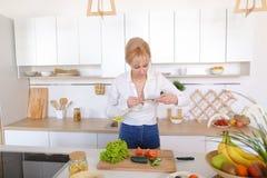 Kulinarisches Mädchen hält Smartphone in den Händen und macht Foto von veget Lizenzfreie Stockbilder