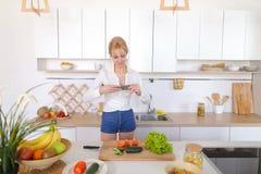 Kulinarisches Mädchen hält Smartphone in den Händen und macht Foto von veget Lizenzfreies Stockbild