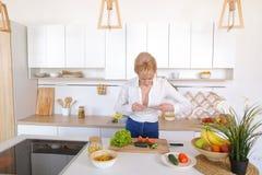 Kulinarisches Mädchen hält Smartphone in den Händen und macht Foto von veget Lizenzfreies Stockfoto