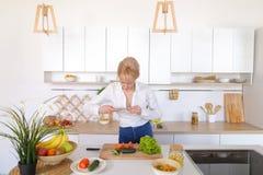 Kulinarisches Mädchen hält Smartphone in den Händen und macht Foto von veget Stockfotos