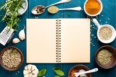 Kulinarisk bakgrund och receptet bokar med kryddor på trätabellen Royaltyfri Fotografi