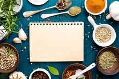 Kulinarisk bakgrund och receptet bokar med kryddor på trätabellen Royaltyfri Foto