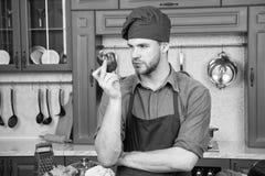 Kulinariskt recept med peppar Kock som lagar mat s?t peppar Vegetarisk kokkonstingrediens Matlagning f?r f?rkl?de f?r mankockkl?d arkivfoto