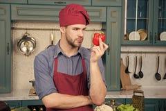 Kulinariskt recept med peppar Kock som lagar mat s?t peppar Vegetarisk kokkonstingrediens Matlagning f?r f?rkl?de f?r mankockkl?d royaltyfria bilder