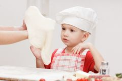 Kulinarna pizza jest zabawą - mały szef kuchni bawić się z mąką Fotografia Stock