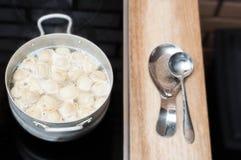 Kulinarne kluchy w aluminiowej niecce na kuchence w kuchni, czekać na czyraka set na stole obrazy stock