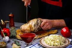 Kulinarnego procesu wieprzowiny Bawarski knykieć z sauerkraut, ostrym chili kumberlandem i piwem w wypiekowej niecce szef kuchni  zdjęcie stock