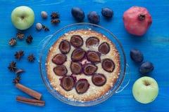 Kulinarny nieociosany śliwka tort na błękitnym drewnianym tle Zdjęcie Royalty Free